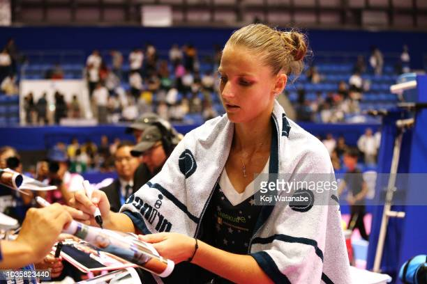 Karolina Pliskova of the Czech Republic signs balls after her victory in the Singles second round match against Daria Gavrilova of Australia on day...