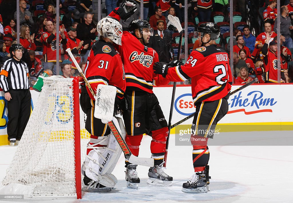Karri Ramo #31, Mark Giordano #5, and Jiri Hudler #24 of the Calgary Flames celebrate after a win against the Ottawa Senators at Scotiabank Saddledome on November 15, 2014 in Calgary, Alberta, Canada.