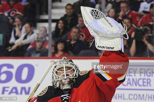 Karri Ramo of the Calgary Flames makes a glove save against the Tampa Bay Lightning during an NHL game at Scotiabank Saddledome on October 21 2014 in...