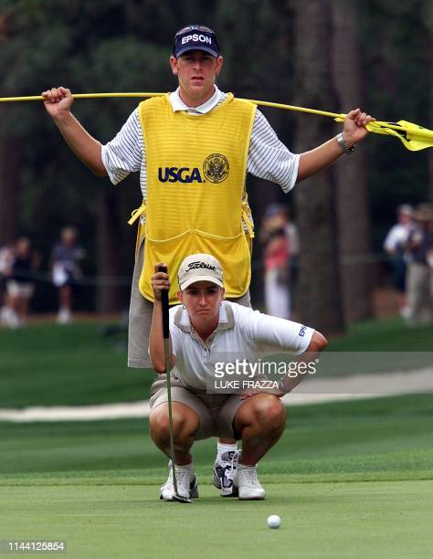 Karrie Webb of Australia lines up a putt as her caddy Mike Patterson stands behind her on the 8th hole 01 June 2001 as they both finished the second...