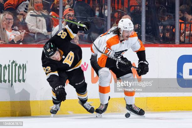 Karson Kuhlman of the Boston Bruins and Zack MacEwen of the Philadelphia Flyers chase the puck during the second period at Wells Fargo Center on...