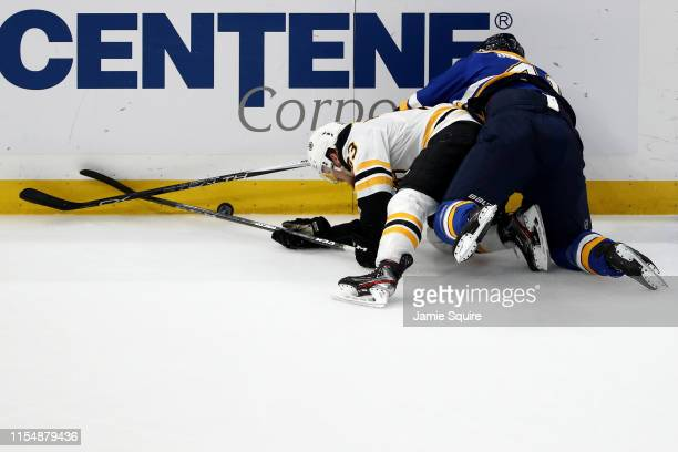 Karson Kuhlman of the Boston Bruins is checked into the boards by Robert Bortuzzo of the St Louis Blues during the first period in Game Six of the...