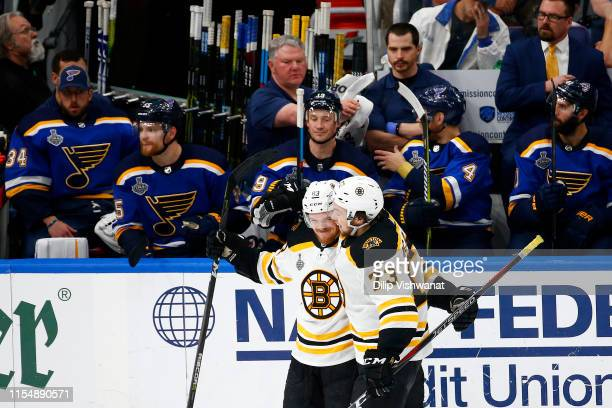 Karson Kuhlman of the Boston Bruins is congratulated by his teammate Charlie McAvoy after scoring a third period goal against the St Louis Blues in...