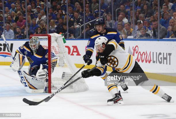 Karson Kuhlman of the Boston Bruins tries to center the puck as Vince Dunn of the St Louis Blues defends the play during the second period of Game...