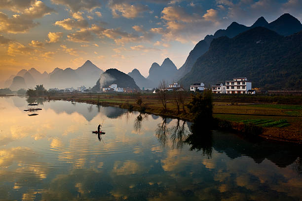 Karst mountains and fisherman on raft on Yulong River.