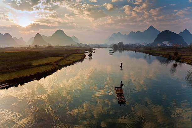 Karst mountains and fishermen on rafts on Yulong River.