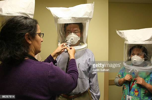 Karya Lustig sprays a chemical mist into a hood as she fits and trains doctors and nurses how to use the N95 respiratory mask at the La Clinica San...
