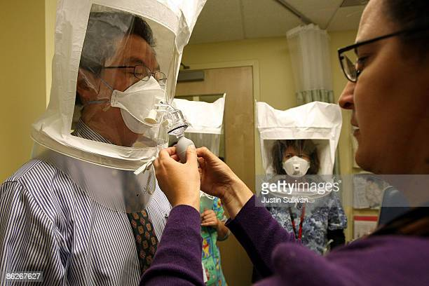Karya Lustig sprays a chemical mist into a hood as she fits and trains doctors and nurses on how to use the N95 respiratory mask at the La Clinica...