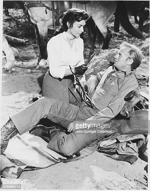Karyl Orton prepares to cauterize a bullet wound in the shoulder of Jim Slater in the 1956 western film Backlash