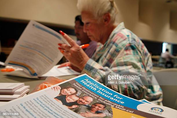 Karyn Jackson, right, helps Fernando Rico, of Pasadena, who doesn't have health care insurance, fill out an a Covered California application for...