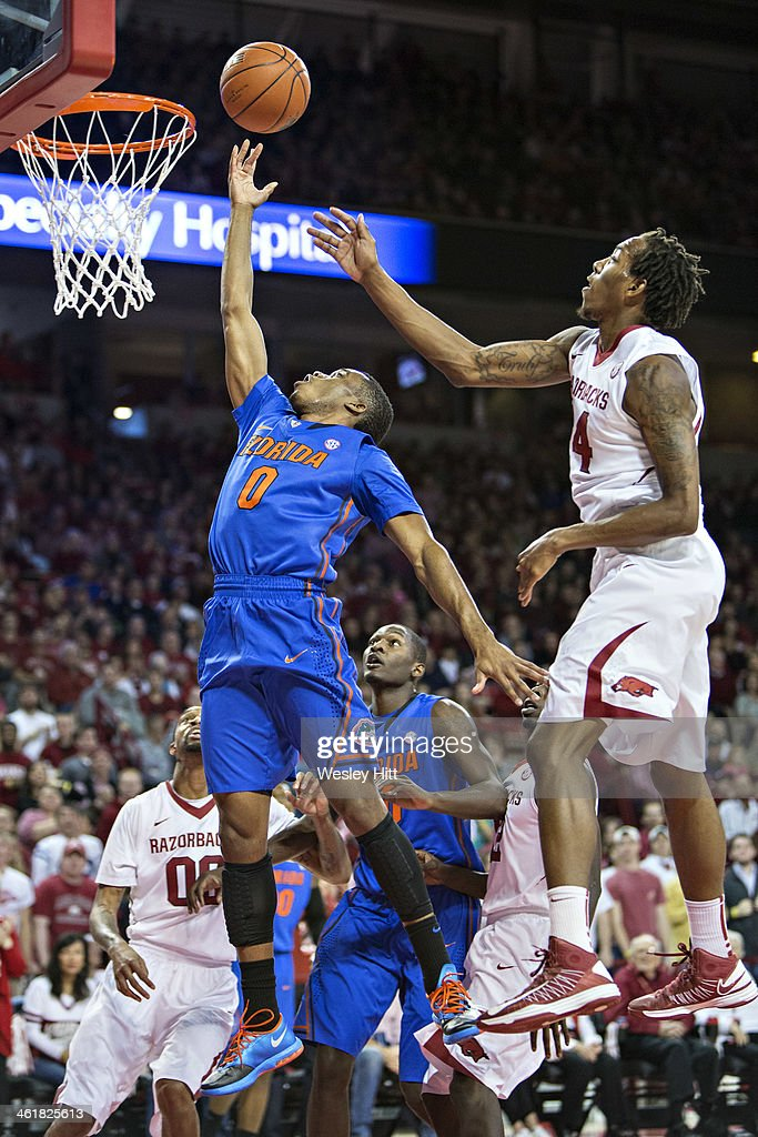 Kasey Hill #0 of the Florida Gators goes up for a shot past Coty Clarke #4 of the Arkansas Razorbacks at Bud Walton Arena on January 11, 2014 in Fayetteville, Arkansas. The Gators defeated the Razorbacks 84-82.