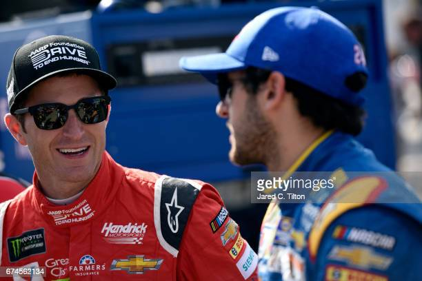 Kasey Kahne driver of the AARP Drive to End Hunger Chevrolet talks with Chase Elliott driver of the NAPA Brakes Chevrolet on the grid during...