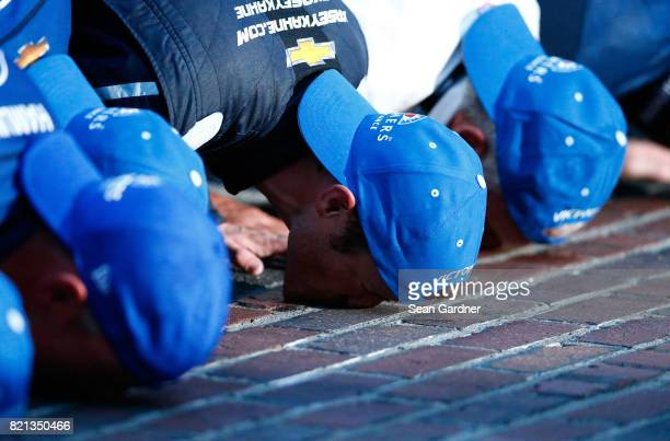 Kasey Kahne driver of the Farmers Insurance Chevrolet kisses the yard of bricks with his crew after winning the Monster Energy NASCAR Cup Series...
