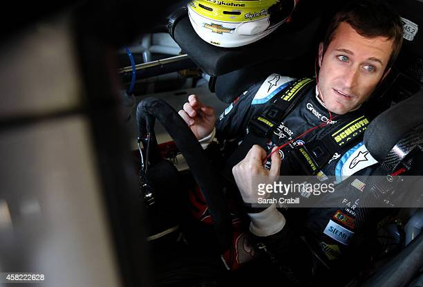 Kasey Kahne, driver of the Great Clips Chevrolet, sits in his car in the garage area during practice for the NASCAR Sprint Cup Series AAA Texas 500...