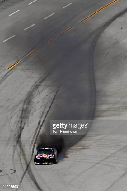 Kasey Kahne driver of the Red Bull Toyota drives down pit road while on fire after an incident in the NASCAR Sprint Cup Series Aaron's 499 at...