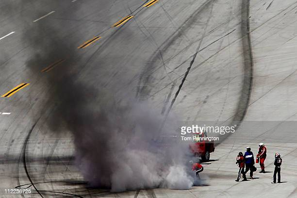 Kasey Kahne driver of the Red Bull Toyota stands by pit road while safety workers extinguish his car after an incident in the NASCAR Sprint Cup...