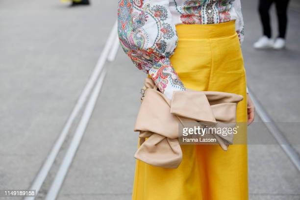 Kash Ohara clutch detail wearing Yves Saint Laurent sunglasses Zimmerman top yellow wide pants at MercedesBenz Fashion Week Resort 20 Collections on...