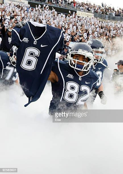 Kashif Moore of the Connecticut Huskies carries out the jersey of murdered teammate Jasper Howard before the game against the Rutgers Scarlet Knights...