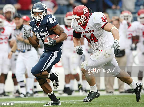 Kashif Moore of the Connecticut Huskies carries the ball as Ryan D'Imperio of the Rutgers Scarlet Knights defends on October 31 2009 at Rentschler...