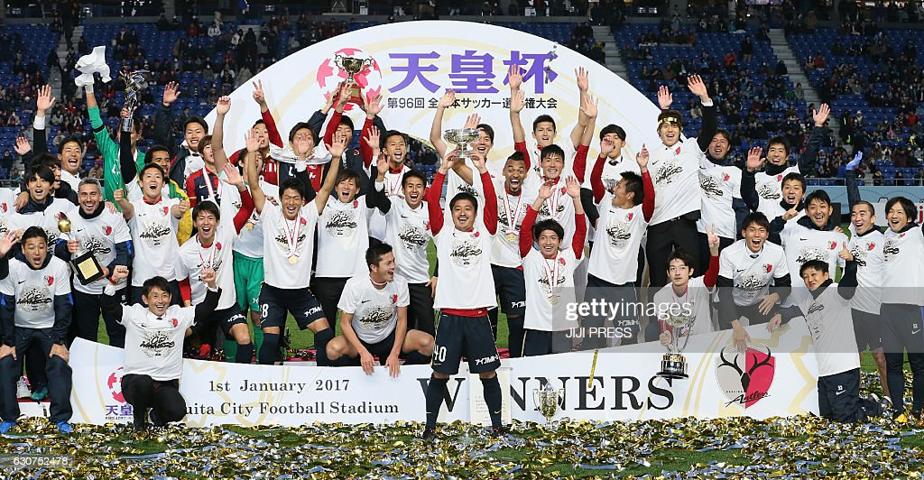 TOPSHOT - Kashima Antlers captain and midfielder Mitsuo Ogasawara (C) raises the Emperor's Cup trophy with his team officials and players after their victory over Kawasaki Frontale at the 96th Emperor's Cup football tournament final match in Osaka on January 1, 2017. / AFP / JIJI PRESS / JIJI PRESS / Japan OUT