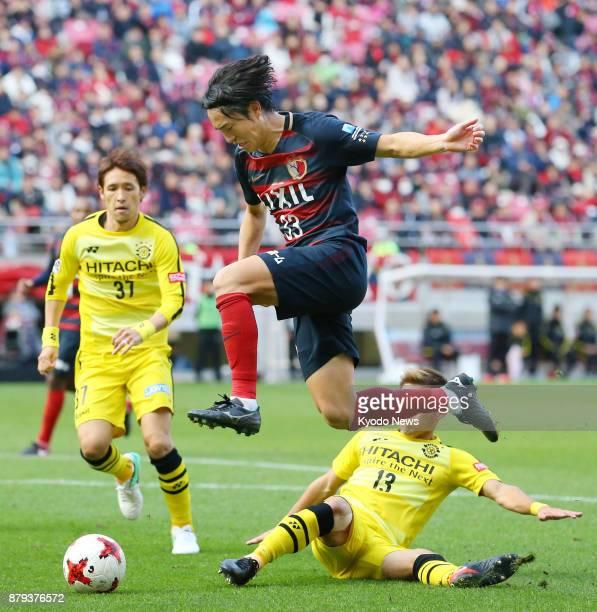 Kashima Antlers' Mu Kanazaki leaps over Kashiwa Reysol's Ryuta Koike with Hajime Hosogai looking on during the second half of a 00 draw in the...