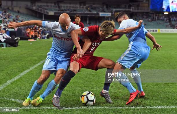 Kashima Antlers player Yuma Suzuki is tackled by Sydney FC players Adrian Mierzejewski and Paulo Retre during their AFC Champions League football...
