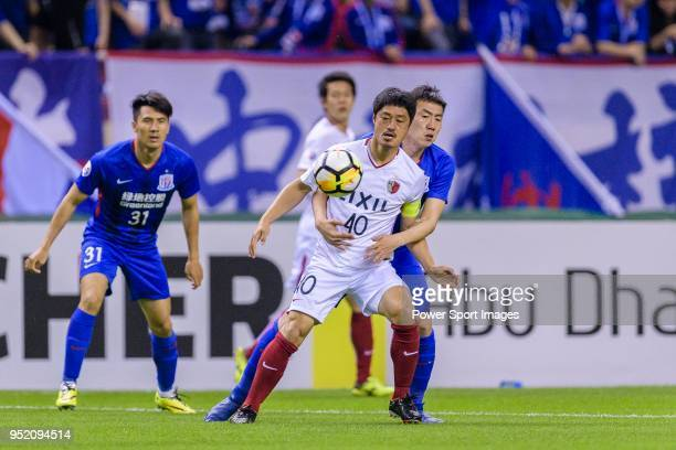 Kashima Midfielder Ogasawara Mitsuo fights for the ball with Shanghai Shenhua Midfielder Qin Sheng during the AFC Champions League 2018 Group Stage F...