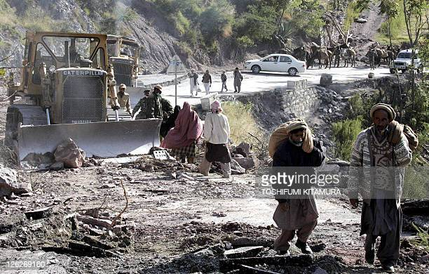 Kashimir residents walk on the opened road to return their mountain villages in Sanghar some eight kilometres north of Balakot 18 October 2005 The...