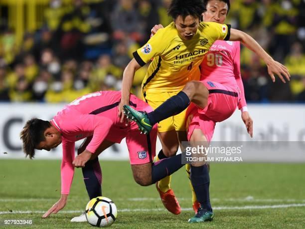 Kashiwa Reysol's defender Shinnosuke Nakatani is sandwiched by Kitchee defenders Li Ngai Hoi and Kim Bong-Jin during the AFC Champions League...