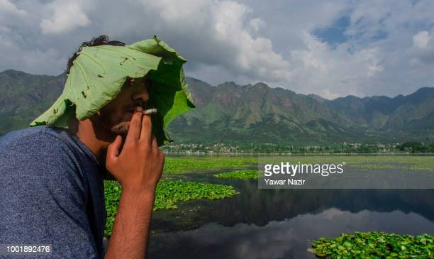 Kashmir boy with a hat made from lotus leaves rests on the parapet of Dal lake on July 19 2018 in Srinagar the summer capital of Indian administered...