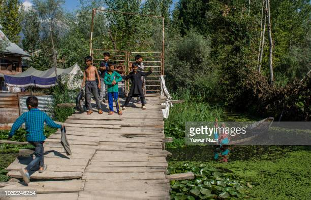 Kashmir children play on a make shift bridge as a woman rows her boat at Dal lakel on September 12 2018 in Srinagar the summer capital of Indian...