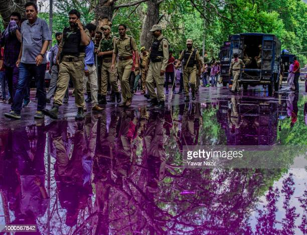 Kashmir government employees and Indian policemen are reflected on the puddle created from the purple dyed chemical water which Indian police fired...