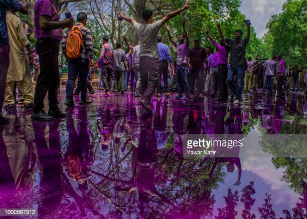Kashmir government employees are reflected on the puddle created by the purple dyed chemical water which Indian police fired from their canons on...