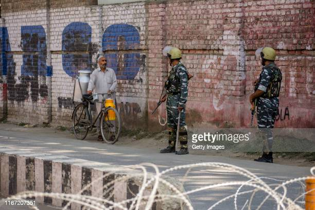 Kashmir hawker selling milk pleads Indian government forces to allow him to cross a concertina razor wire laid on road by them as they guard the...