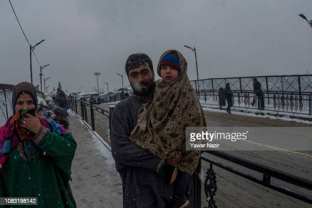 Kashmir man carries his daughter in his lap amid fresh snowfall on January 16 2019 in Srinagar the summer capital of Indian administered Kashmir...