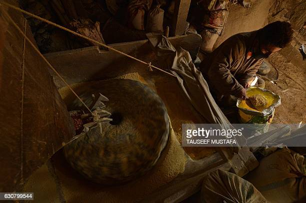 A Kashmir man checks the powder after grinding the maize with a waterrun grinder near Kokernag south of Srinagar on January 2 2017 A cold wave...