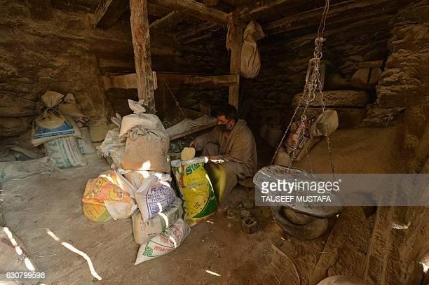 A Kashmir man checks the powder maize after grinding the maize with a waterrun grinder near Kokernag south of Srinagar on January 2 2017 A cold wave...
