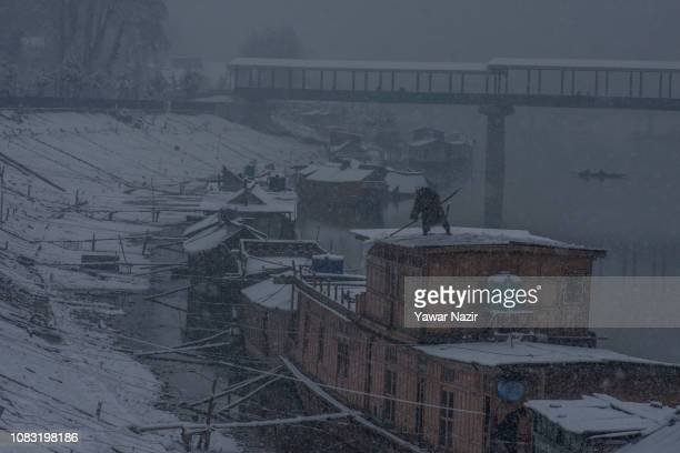 Kashmir man removes snow from his houseboat amid fresh snowfall on January 16 2019 in Srinagar the summer capital of Indian administered Kashmir...
