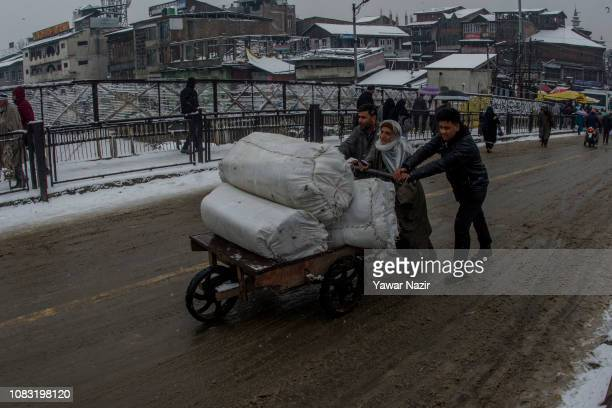 Kashmir men help an elderly man to push his hand cart on a snow covered steep road amid fresh snowfall on January 16 2019 in Srinagar the summer...