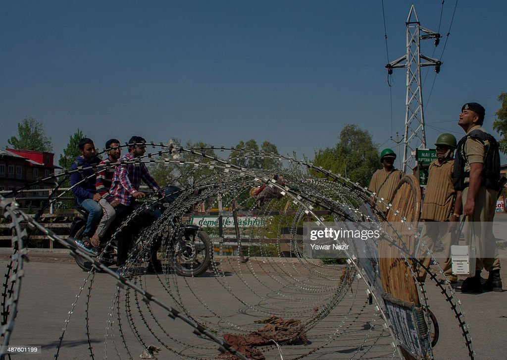Kashmir men on a motor cycle seek permission from Indian paramilitary soldier to cross the concertina razor wire during a curfew following a killing of a youth on May 01, 2014 in Srinagar, the summer capital of Indian-administered Kashmir, India. Kashmir remained on boil a day after a youth was shot dead by Indian armed government forces in the Old City of Srinagar. Two persons including a woman were also wounded when Indian forces fired at Kashmiri stone hurling protesters who were shouting 'down with India' slogans. The Indian forces in Kashmir clamped a stringent curfew in the region to stop anti-India protests from escalating while as a shutdown was observed to protest the killing of the youth.