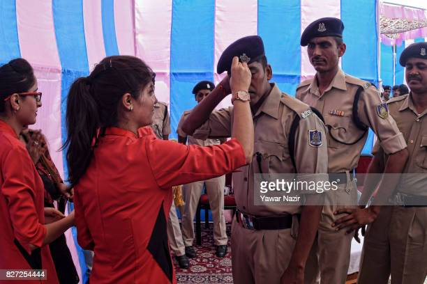 Kashmir Muslim girls in red dress tie Rakhis or votive threads on the wrist of Indian paramilitary troopers at the airport during Raksha Bhandhan on...