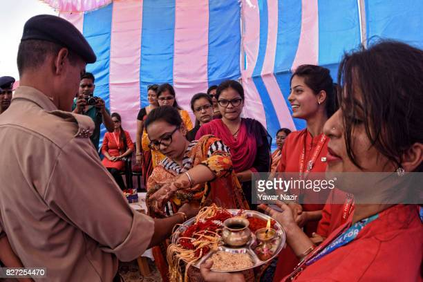 Kashmir Muslim girls in red dress wait to tie Rakhis or votive threads on the wrist of Indian paramilitary troopers at the airport during Raksha...