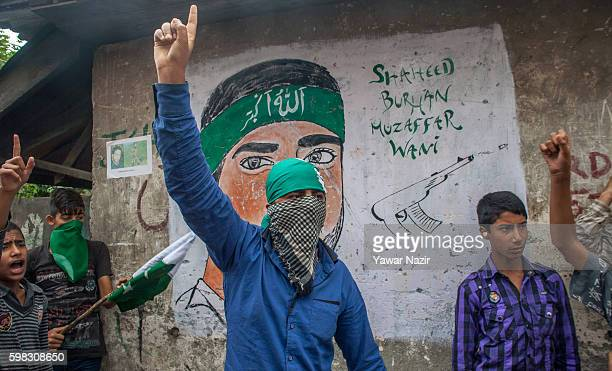 Kashmir Muslim protester shouts antiIndian slogans in front of a mural of young rebel commander Burhan Wani who was killed by Indian government...