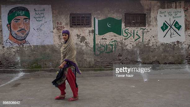 Kashmir Muslim woman walks in front a mural of young rebel commander Burhan Wani who was killed by Indian government forces following weeks of...