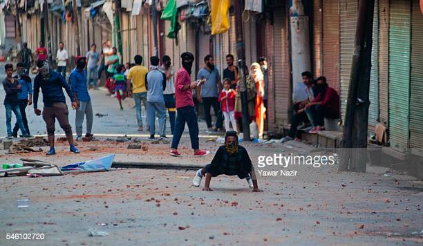 Kashmir protesters taunt Indian policemen after throwing stones at government forces during a curfew on July 11 2016 in Srinagar the summer capital...