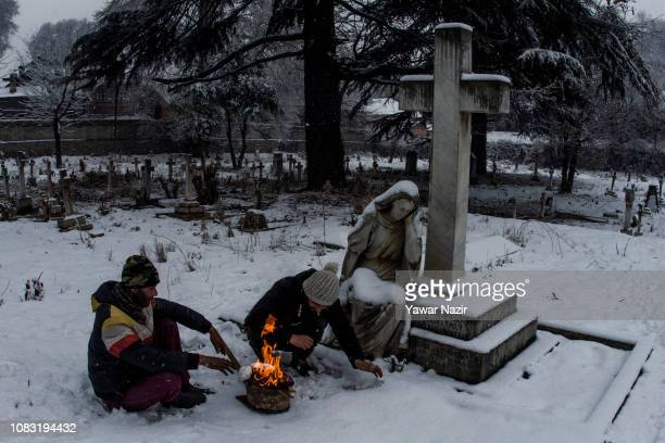 Kashmir workers warm themselves on a bonfire in front a statue in a Christian cemetery during a fresh snow fall on January 16 2019 in Srinagar the...