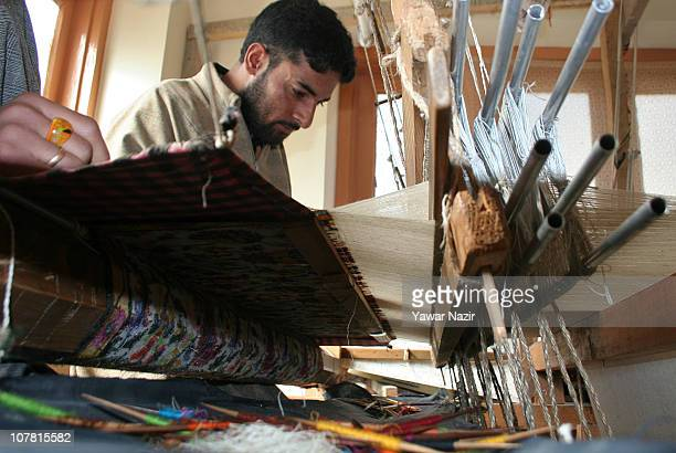 Kashmiri artisans work on a woven Kani or Jamewar shawl at their workshop December 29 2010 on the outskirts of Srinagar the summer capital of Indian...
