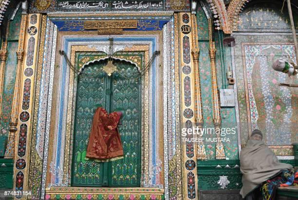 A Kashmiri attendent sits at the door to the KhankaheMoula at the Sayyid Ali Hamadani shrine in Srinagar on November 16 2017 A thunderbolt struck the...