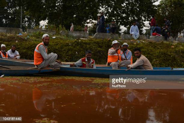 A Kashmiri boat men seen sitting on their boats in the thick mat of red algae seen spread on top of the Dal Lake on September 29 2018 in Srinagar the...