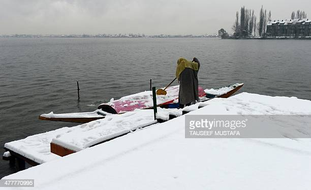 A Kashmiri boatman clears snow from his shikara boat on Dal Lake following heavy snowfall in Srinagar on March 112014 Indianadministered Kashmir has...